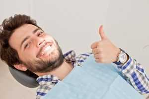 A man smiling and giving a thumbs up at the dentist