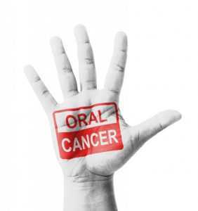 """Hand with an """"Oral Cancer"""" message"""