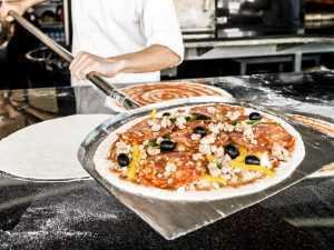 Uncooked pizza on a steel peel