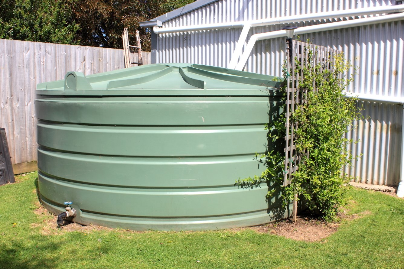 Large eco- friendly water storage tank in suburban backyard