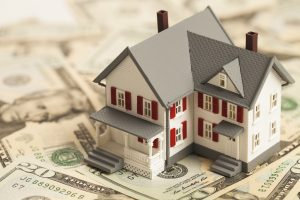 Single family house figure on pile of money