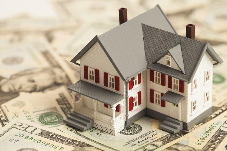 Single family house figure on pile of money