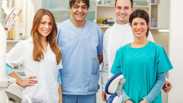A dentist and his team posing together and smiling