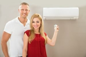 Couple posing for the camera while turning on the air conditioner