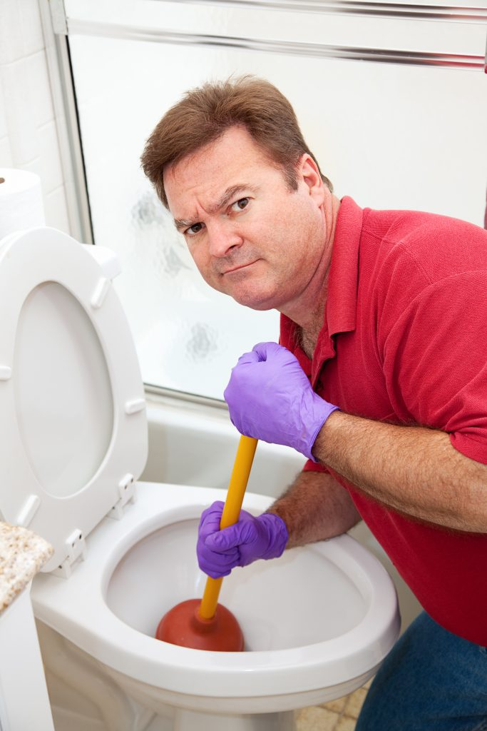 a not-so-happy man trying to unclog his toilet