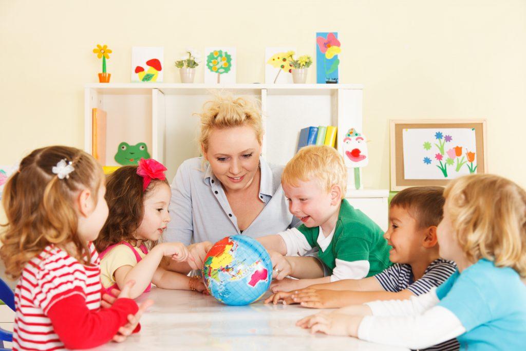 Teacher teaching about the globe to preschoolers