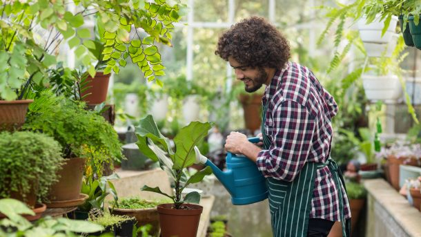 A man watering his plants and smiling