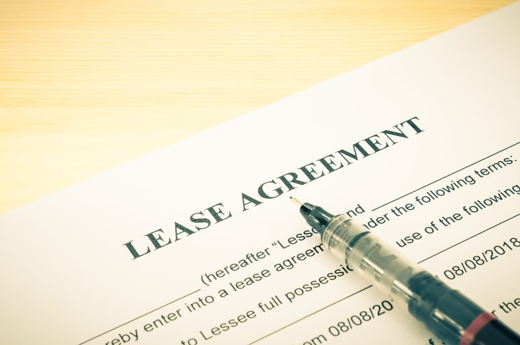 Lease agreement contract sheet and brown pen at bottom right corner