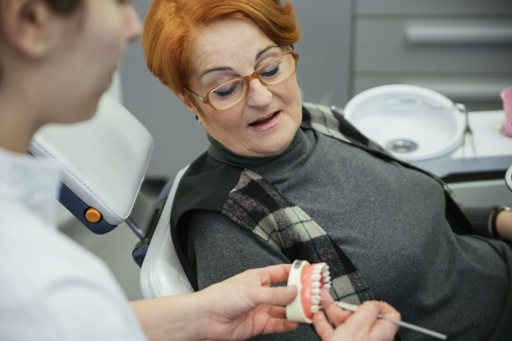 Dentist explaining to an old woman