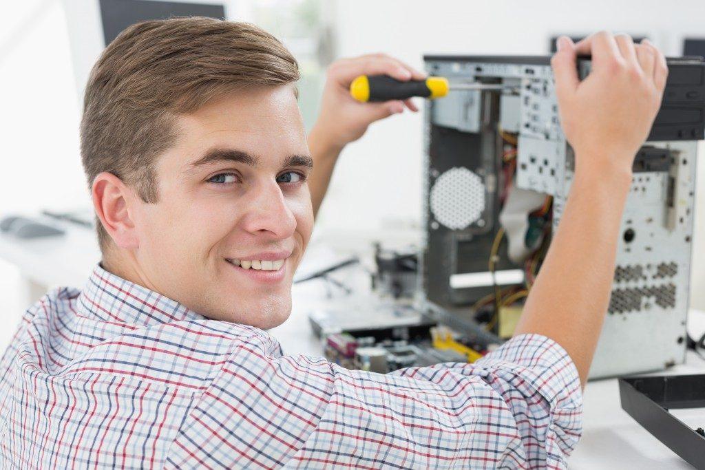 A smiling computer technician
