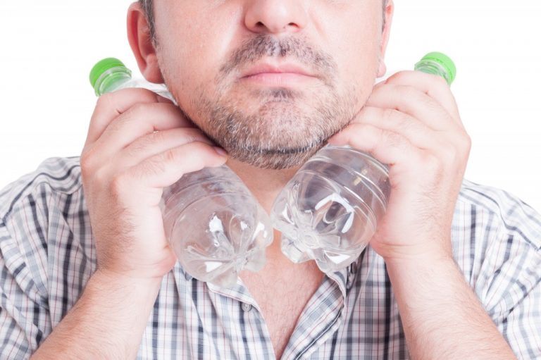Man cooling his neck with cold bottled water