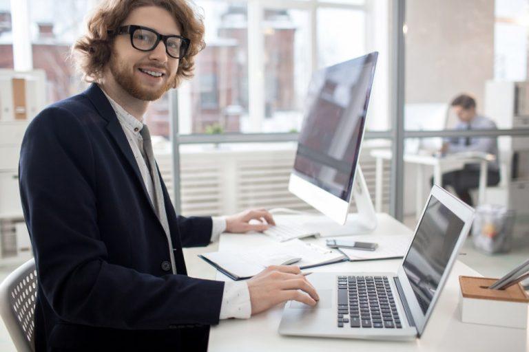 man working on his laptop and desktop