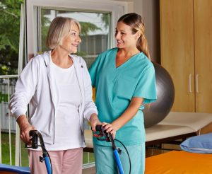 Elderly Woman Assisted by Caregiver
