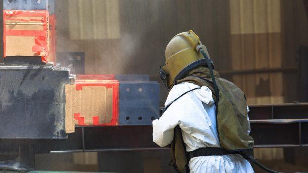 photo of a man sandblasting