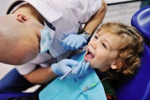 Dentist examines child's teeth