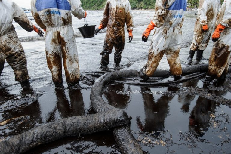people cleaning up oil spill