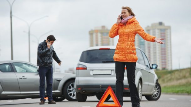 photo of two people involved in a car accident and both of them are talking to their phones