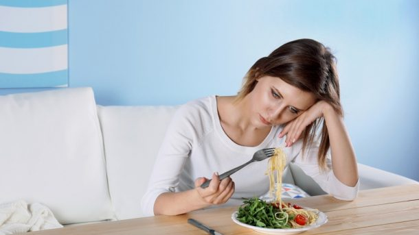 photo of a woman suffering from eating disorder, having a hard time eat her meal