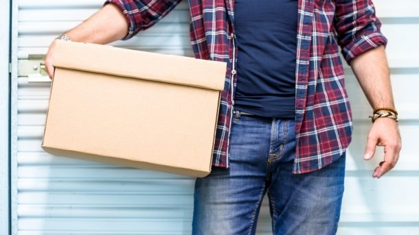 photo of a man holding a box in front of his garage