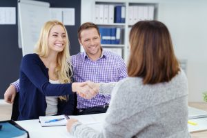 a couple shaking hands with property manager