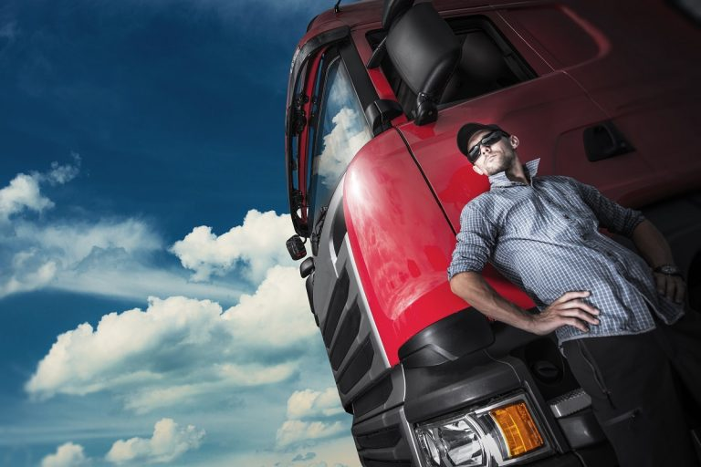 Truck driver posing beside a red truck