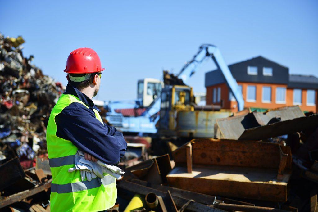 man supervising scrap metal yard
