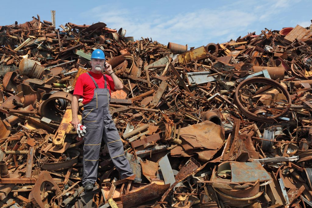 a man standing on a heap of scrap metals