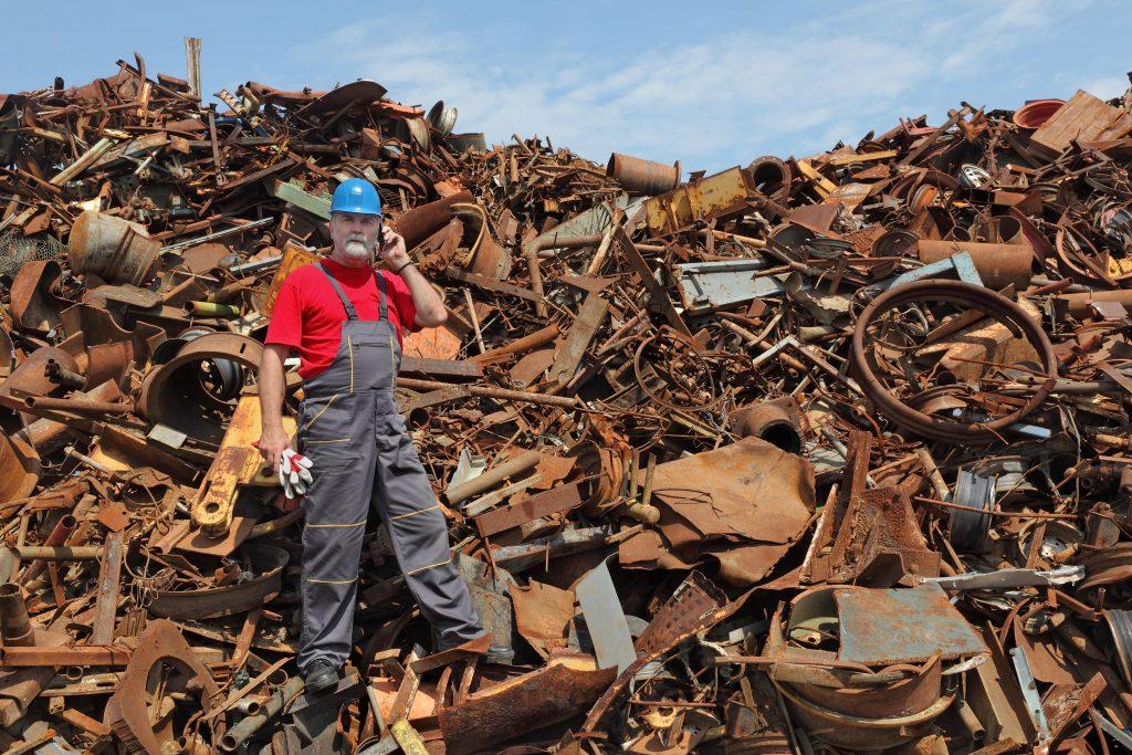 a man standing on a heap of scrap metals