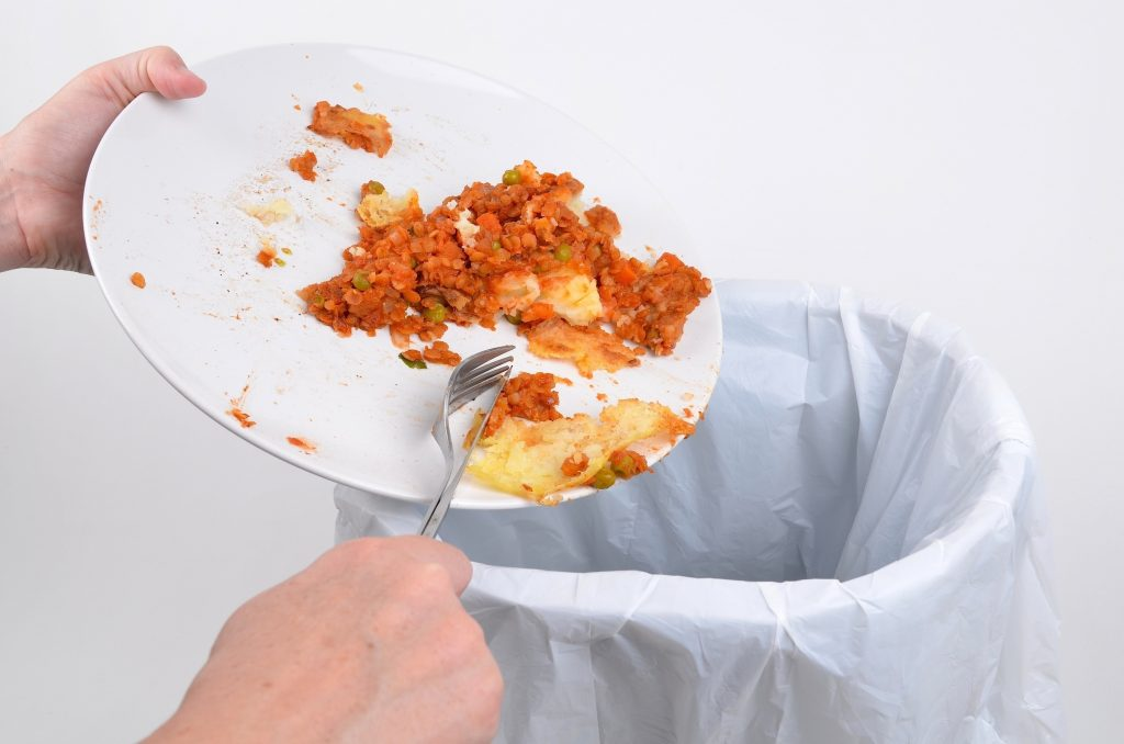 Leftover food being thrown in the trash can