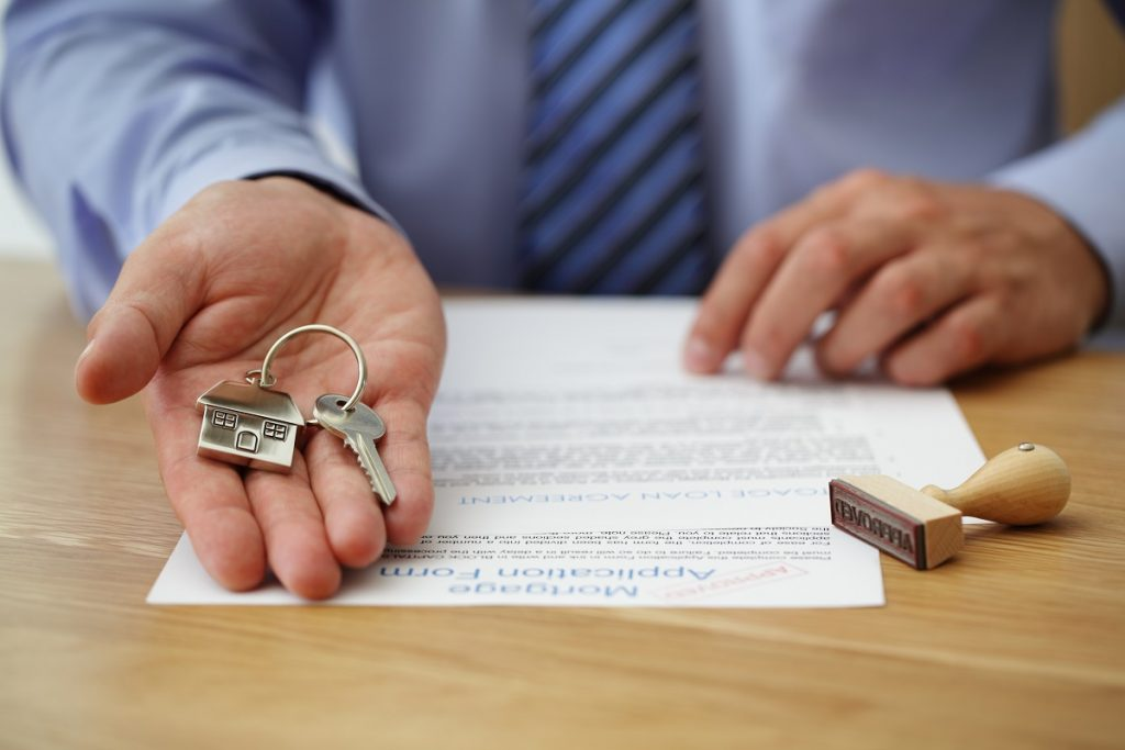 Person holding a key and mortgage application form