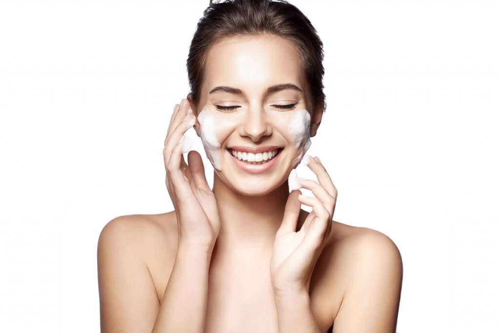Woman happily cleansing her face