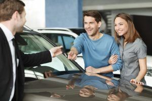 car rental service giving keys to couple