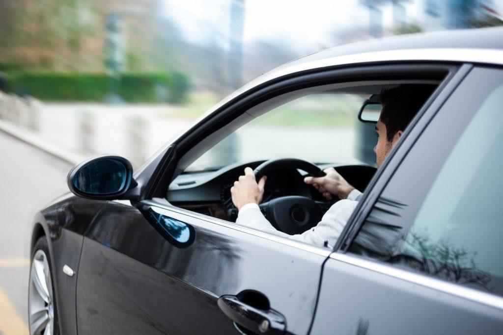 Man driving a black car