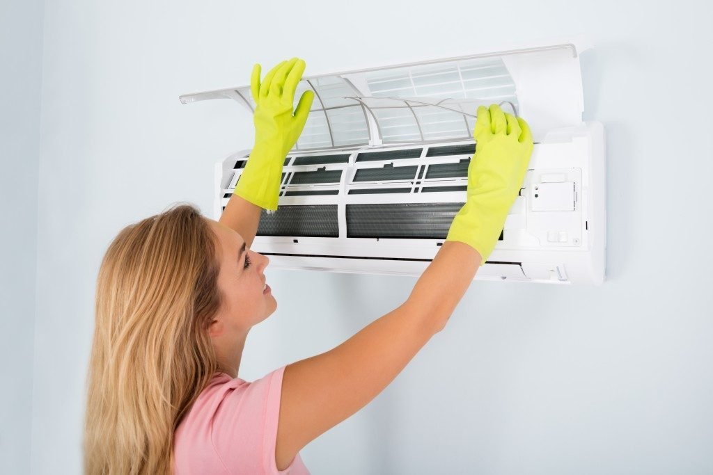 Woman Checking And Cleaning Air Conditioning System
