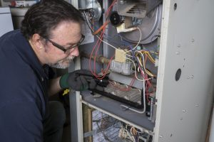technician fixing a gas furnace