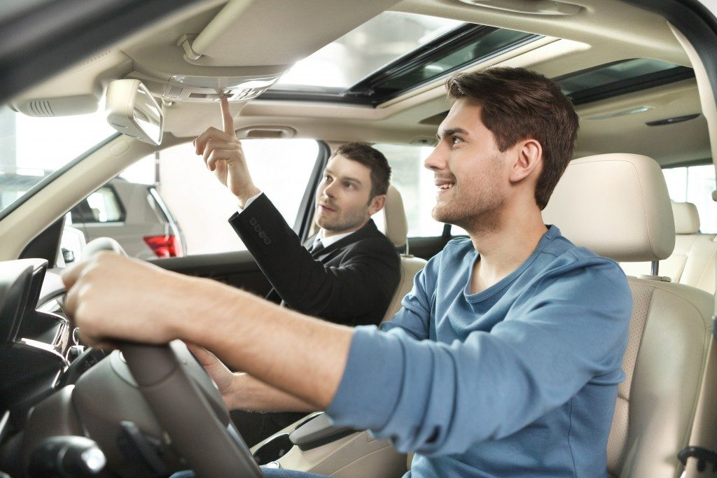 sales man showing potential buyer interior features of car