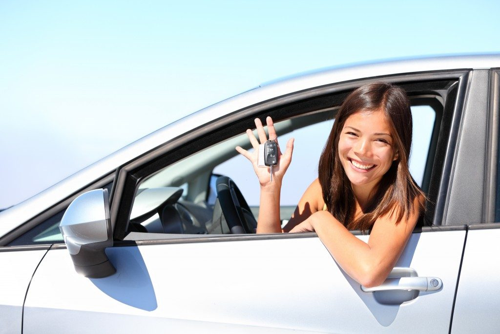 woman smiling happily in her new car