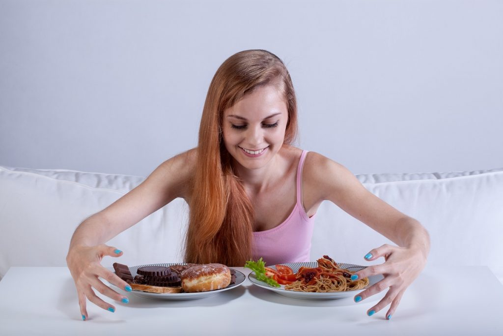 Woman about to eat dessert and pasta