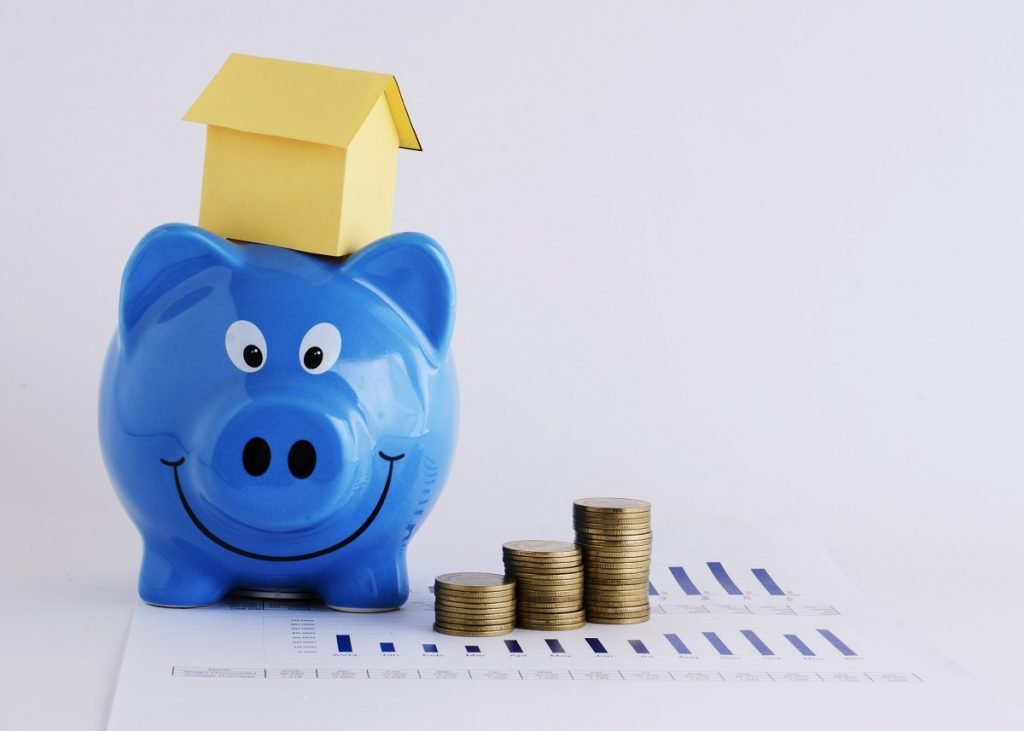 Piggy bank, coins and paper house