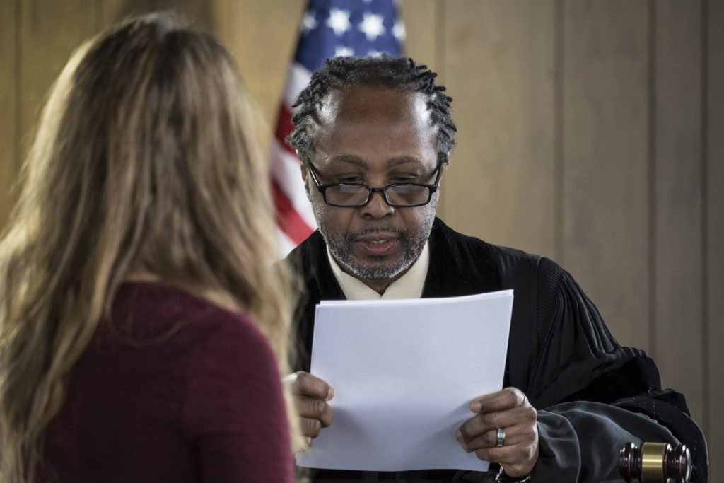 judge reading a document presented by a lawyer
