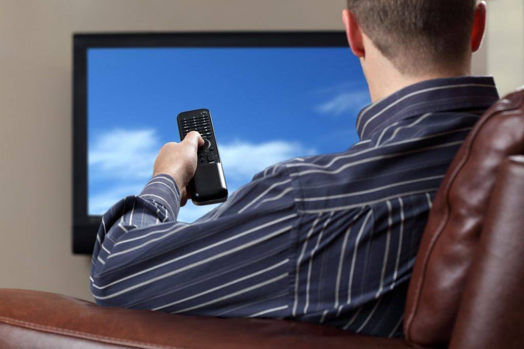 man watching on a flat screen tv