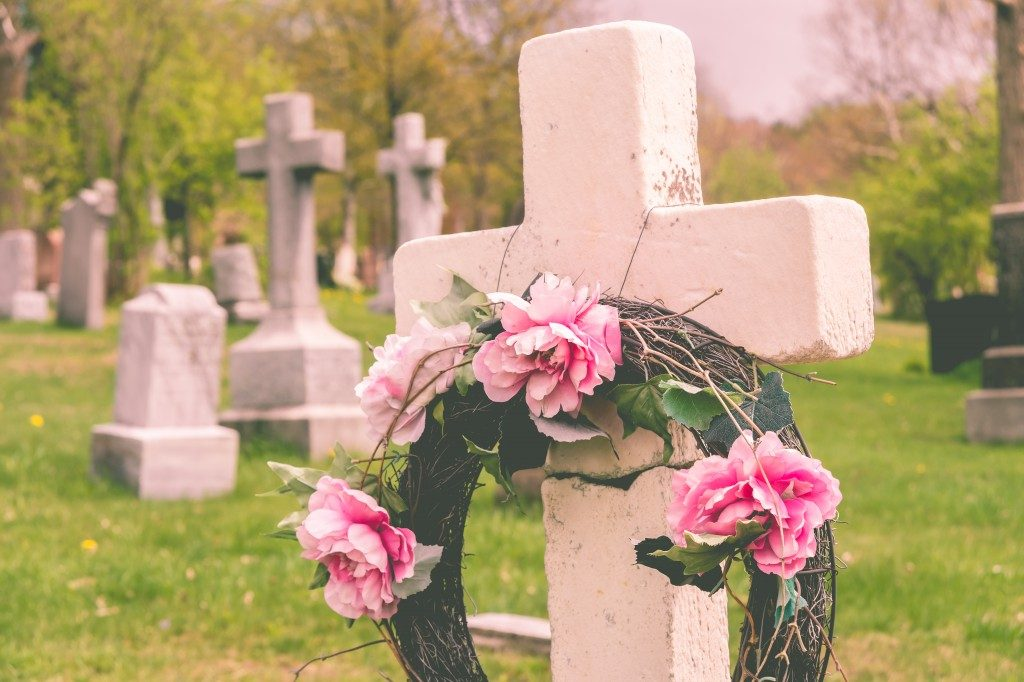 Funeral wreath with pink flower on a cross, in a cemetery, with a vintage filter.
