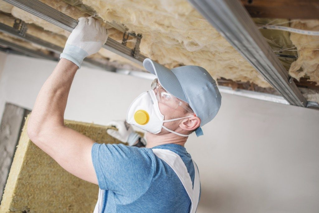 worker repairing ceiling insullation