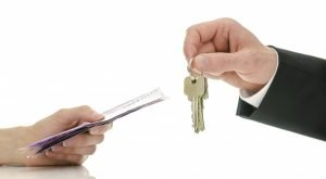 mortgage payment concept, hands exchanging money and house keys