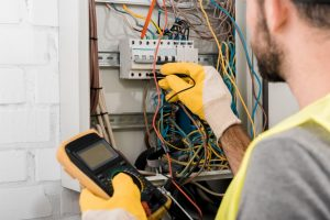 man checking the wires in the circuit box