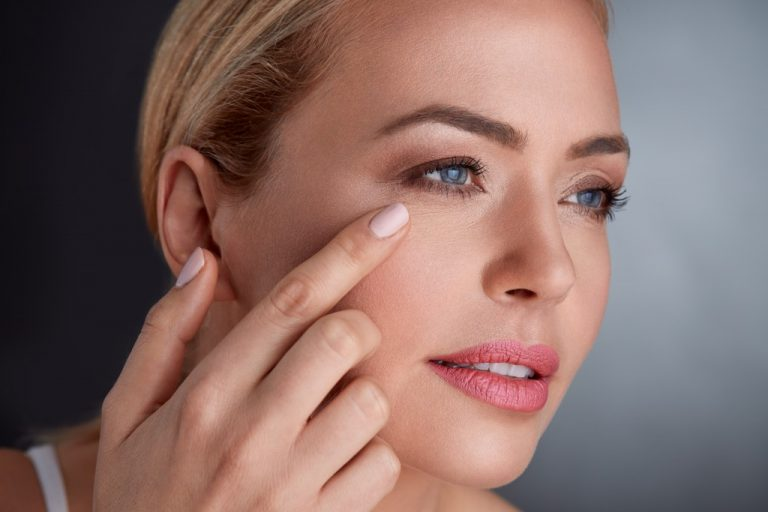 woman pointing at the wrinkles around her eyes