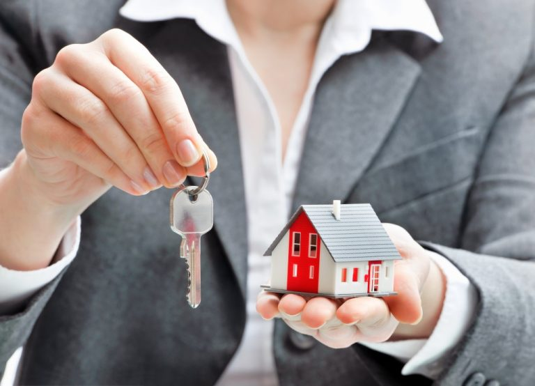 woman holding keys and house model
