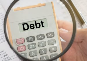 debt text on calculator and magnifier