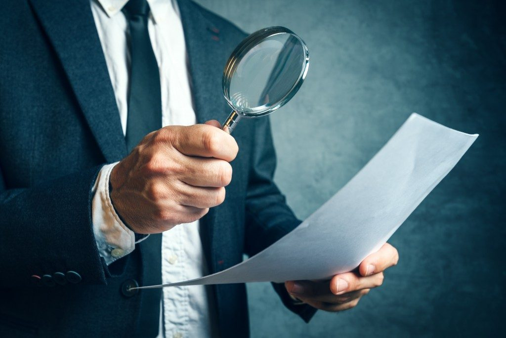 man in a suit looking at document with magnifying glass