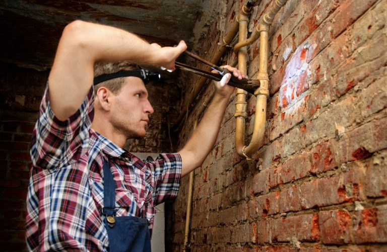 man wearing headlight fixing a leak with a pipe wrench in basement